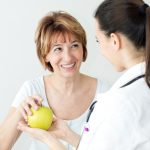 Young female doctor giving to happiness mature woman an apple.